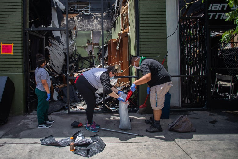 People wearing masks and gloves sweep debris into a garbage bag and survey the damage