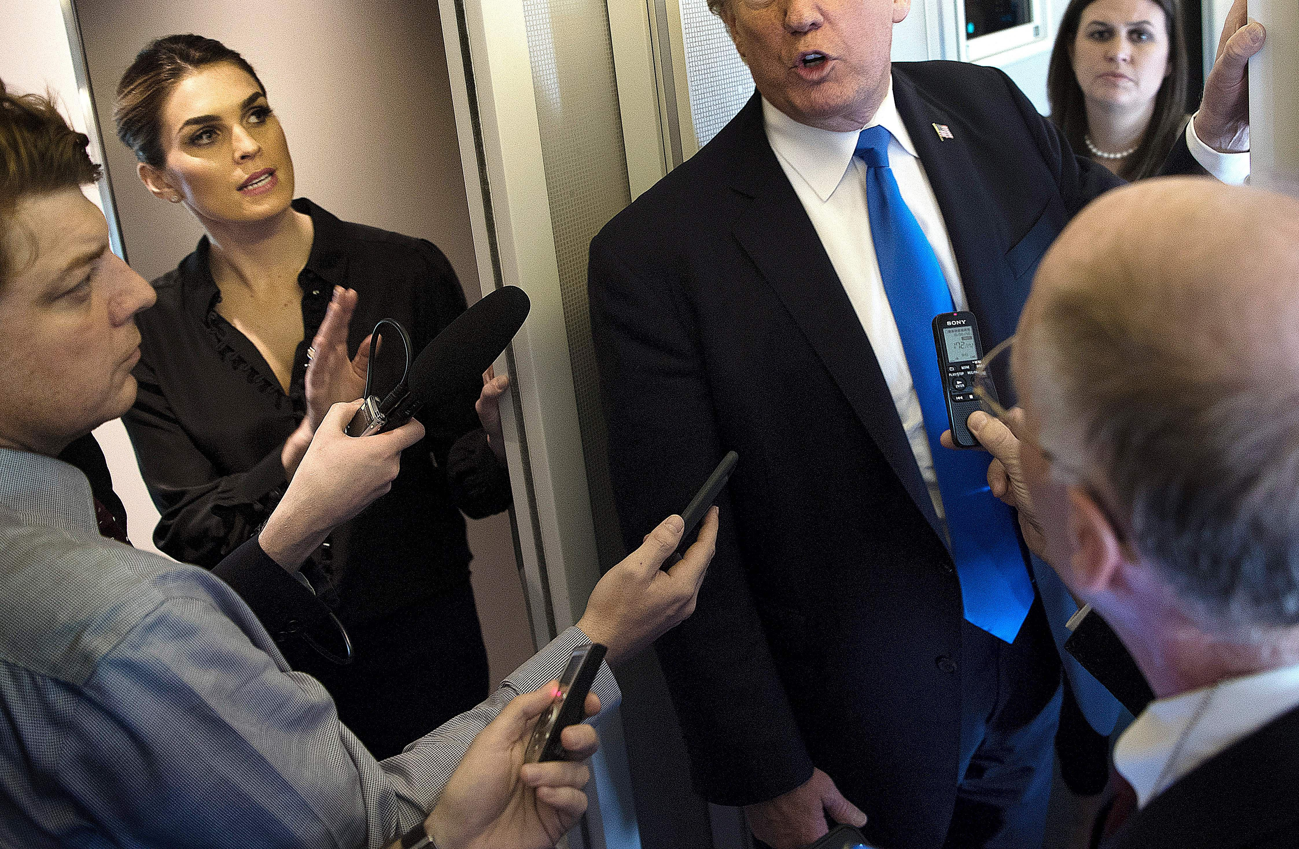 White House Communications Director Hope Hicks and President Trump speak to reporters aboard Air Force One while departing Manila on Nov. 14, 2017.