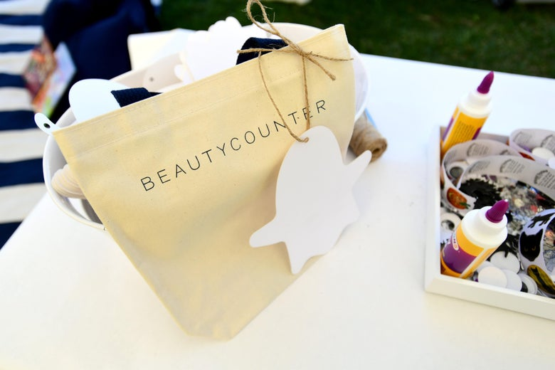A yellow gift with Beautycounter on it sits on a white table.