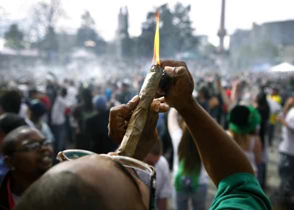 A person identifying himself as Jermagisty Tha King of Denver lights up a 28 ounce blunt at exactly 4:20 p.m. as thousands gathered to celebrate the state's medicinal marijuana laws.