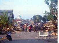Villagers wearing surgical masks rummage through debris