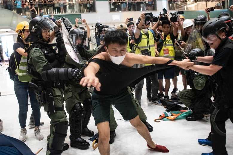 A man tries to escape the grasp of police officers who are tearing his shirt during a protest in a Hong Kong shopping mall.
