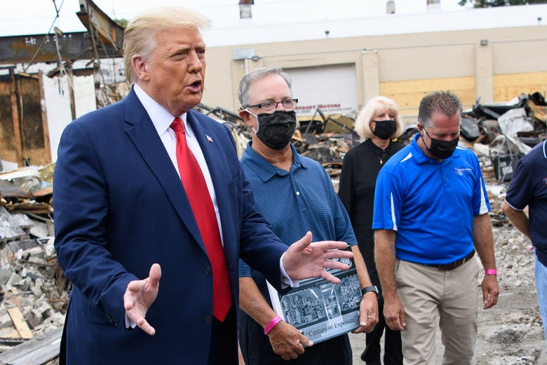 Trump gestures with his hands and speaks while standing amid rubble next to people in face masks.