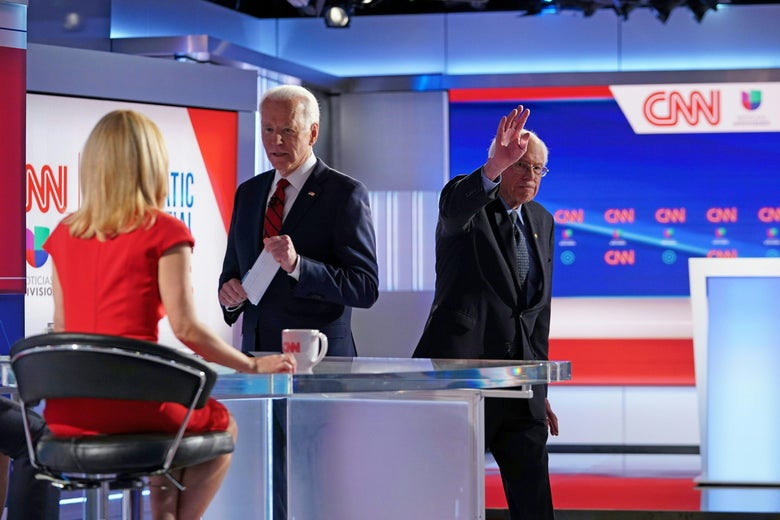 Joe Biden speaks to Dana Bash as Bernie Sanders waves and leaves the debate stage