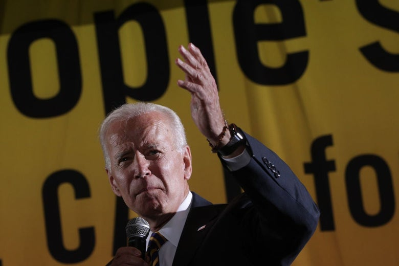 Joe Biden holds a microphone and gestures in front of a large banner.