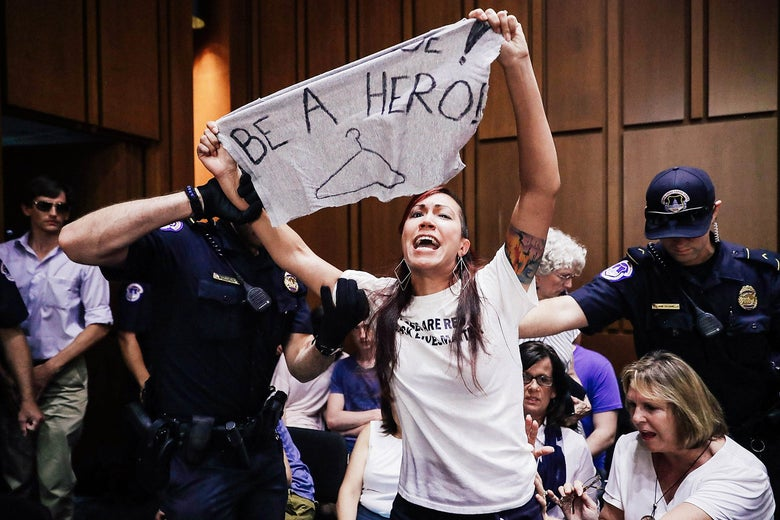 Capitol Police remove a protester from the hearing room during confirmation hearings for Brett Kavanaugh.