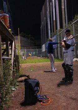 Bullpen catcher Dan McNamara stretches (foreground) as Jorge Vasquez warms up behind him.