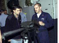 Gunner's mate first-class Mark Napoli demonstrates a Mark 19 Automatic Grenade Launcher to Mark Mazzetti