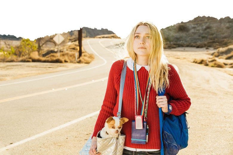 Dakota Fanning walks along a road with a small dog in her bag in Please Stand By.