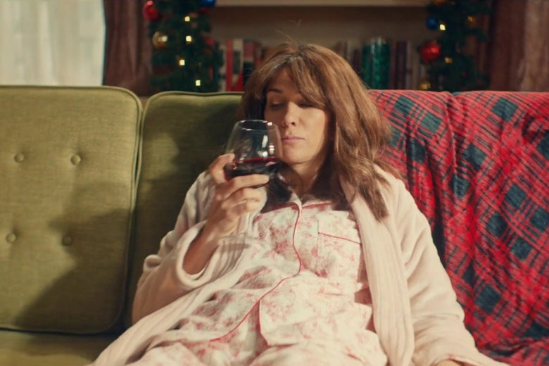 Kristen Wiig slouches on a couch in a living room covered with Christmas decorations, wearing a new robe, drinking a large glass of red wine.