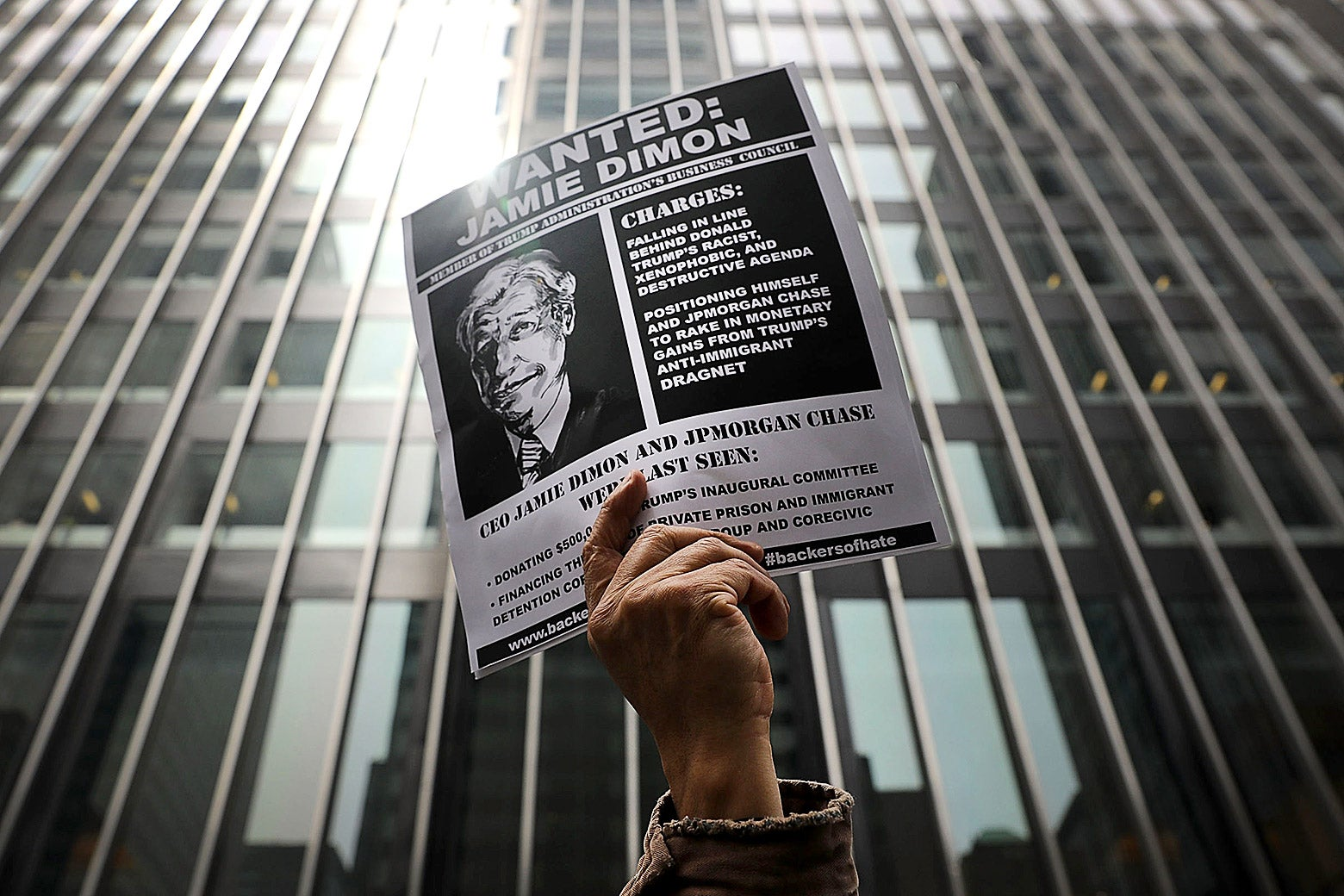 A mockup of a wanted poster for JPMorgan CEO Jamie Dimon is held outside his apartment in New York City.