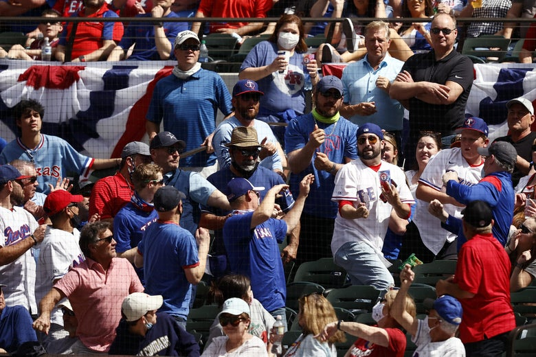 Fans in the stands scramble for a foul ball in the second inning
