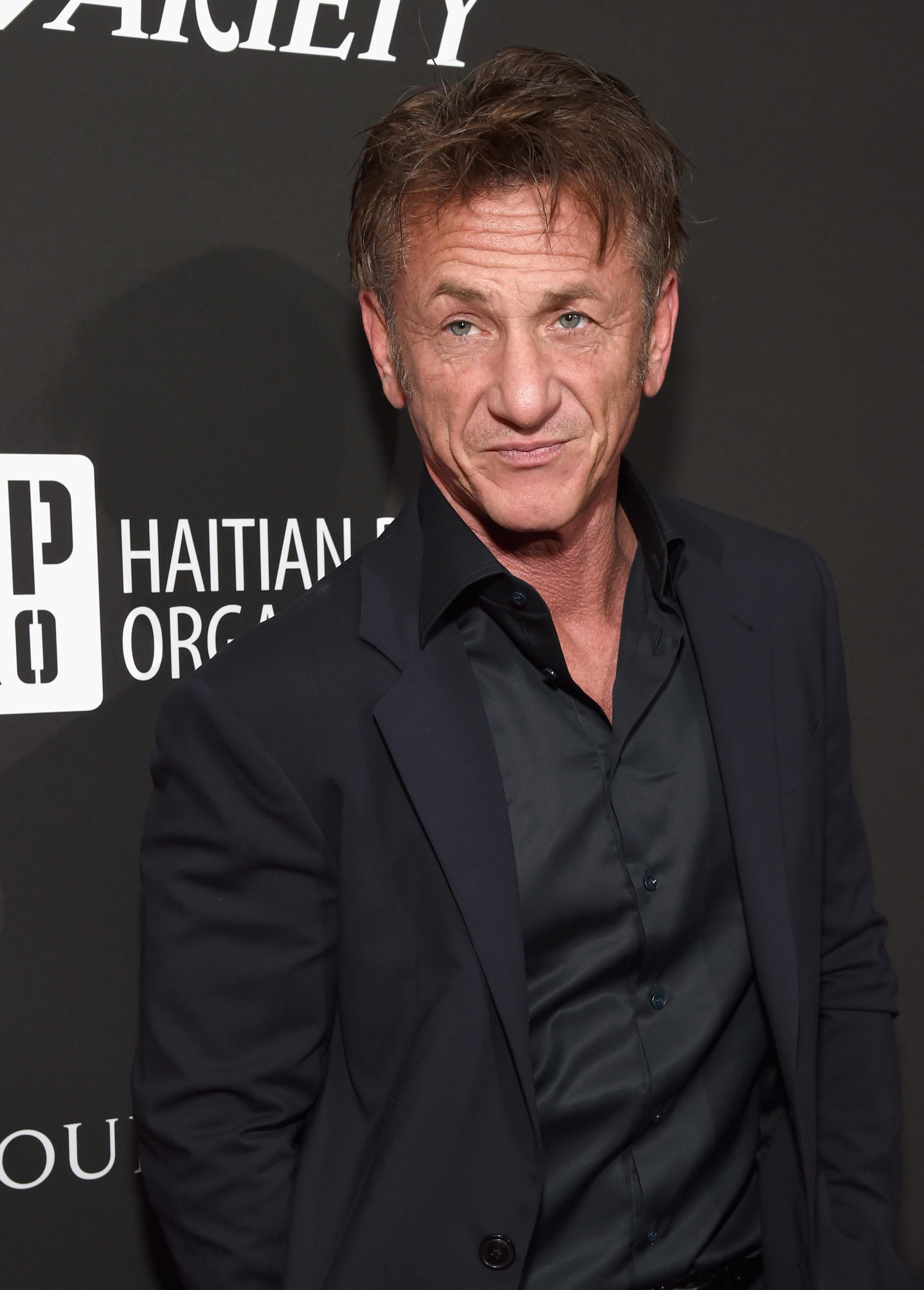 Sean Penn stands in front a black wall, wearing a black suit.