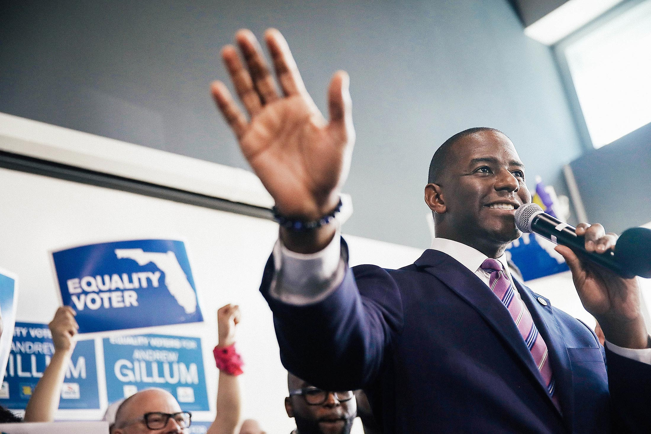 Andrew Gillum speaks into a microphone at a campaign rally.