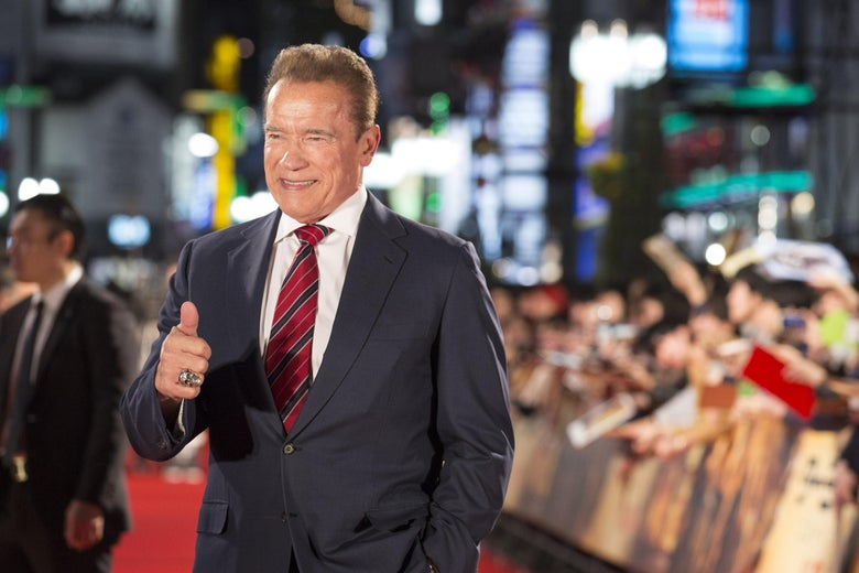 Arnold Schwarzenegger smiles and makes a thumbs-up on the red carpet, with cheering fans in the background