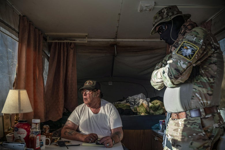 A man dressed in camo and a mask speaks with a man in a T-shirt inside a camper.