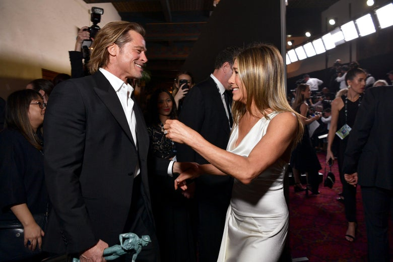 Brad Pitt and Jennifer Aniston  smiling at each other on a red carpet.