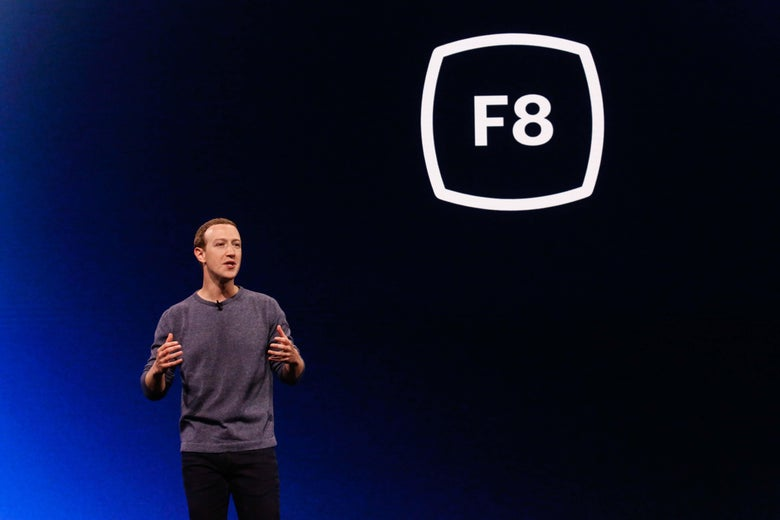 """Facebook CEO Mark Zuckerberg stands in front of a backdrop that reads """"F8."""""""