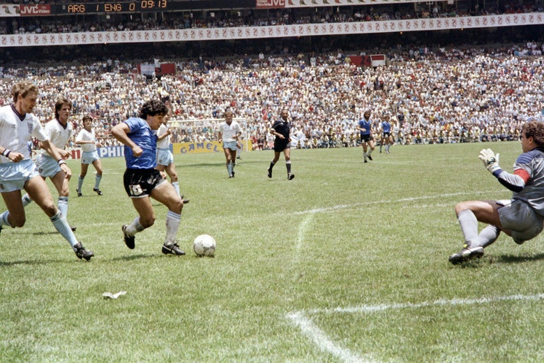 Maradona runs past English defender Terry Butcher on his way to dribbling goalkeeper Peter Shilton, already on the ground, and scoring