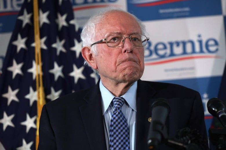 Bernie Sanders frowning in front of a mic