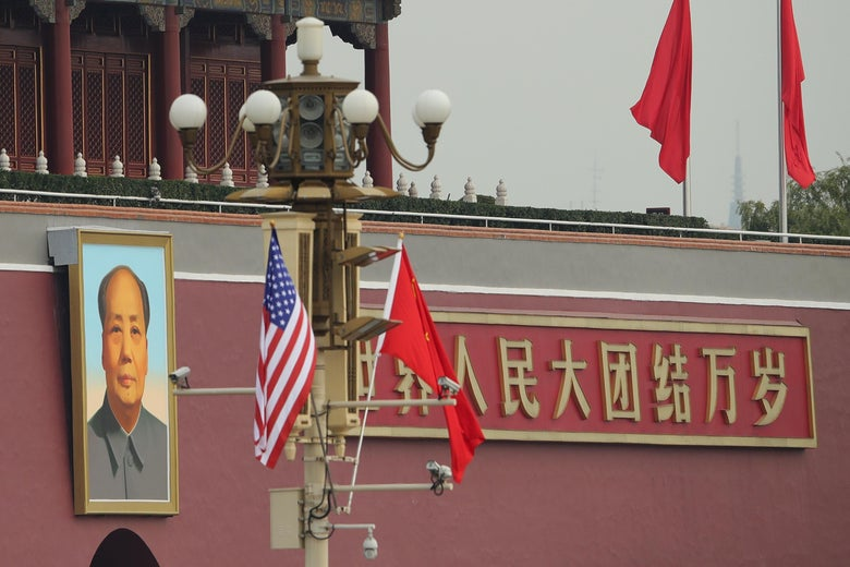 A U.S. flag and a Chinese flag hang on a pole in front of the portrait of Mao Zedong outside the palace