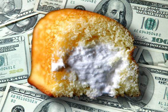 Hostess Twinkie hovering over pile of US Currency.