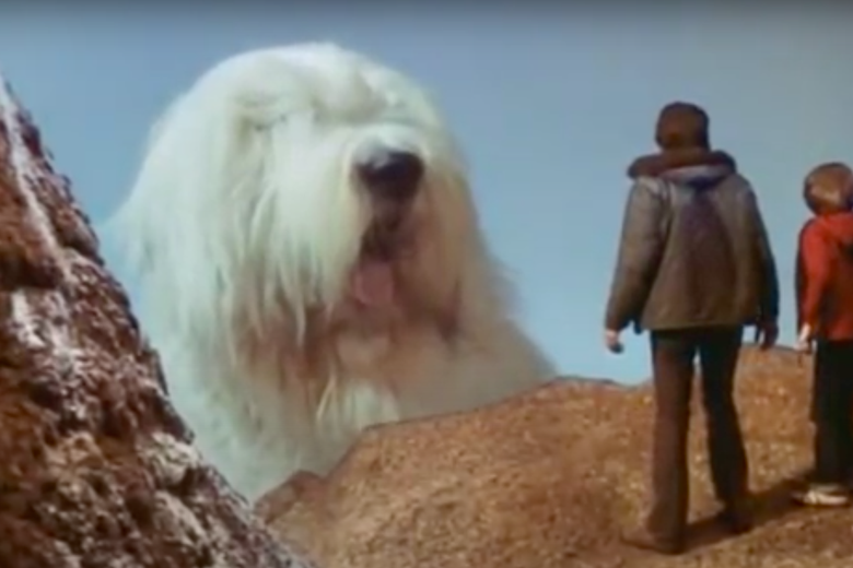 A gigantic sheepdog looms over two tiny humans.
