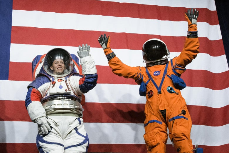 Two people stand in front of an American flag wearing spacesuits, with their hands raised in a waiving motion.