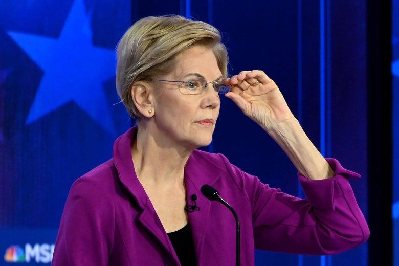 Elizabeth Warren adjusts her glasses while standing at a debate podium.