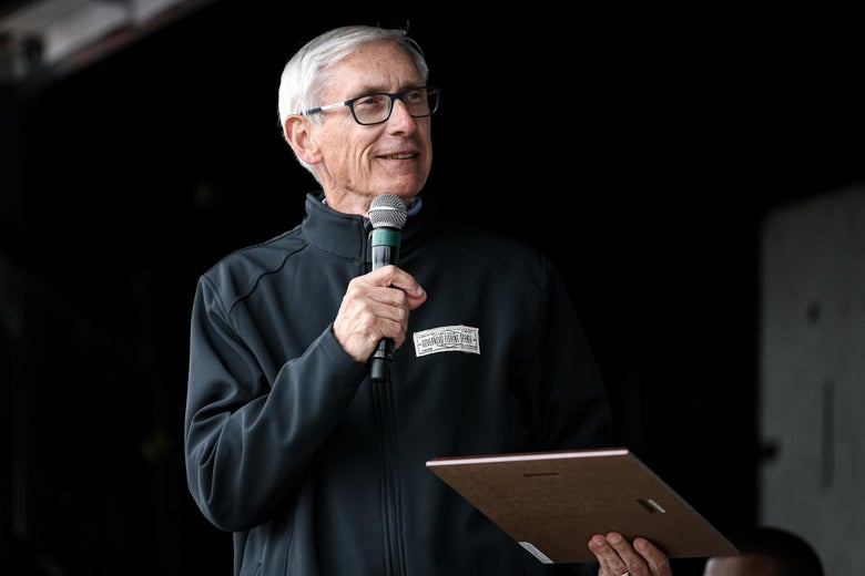 Evers speaks to the crowd, holding a mic in one hand and a clipboard in the other