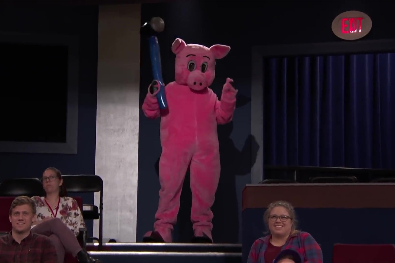 A person in a pig costume wielding an inflatable mallet at the back of the Conan set.