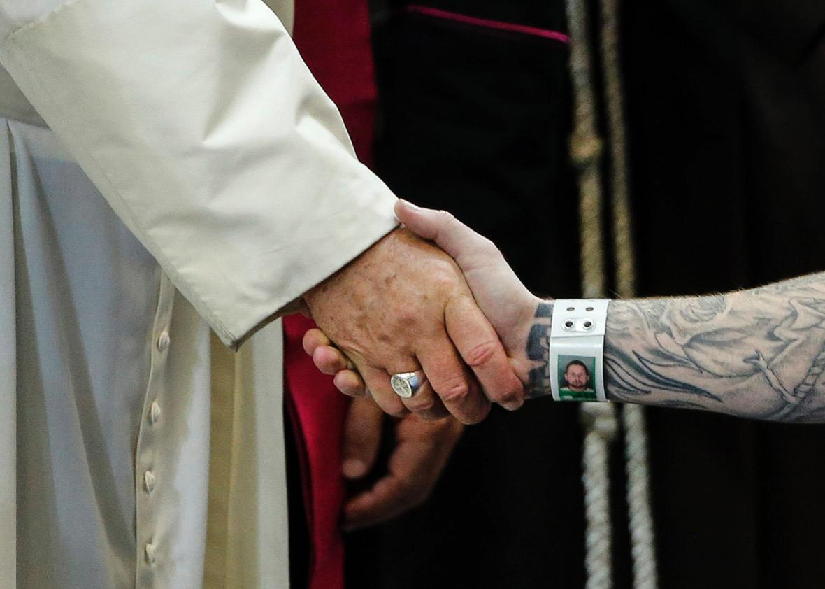 Pope Francis shakes hands with an inmate as he meets with prison