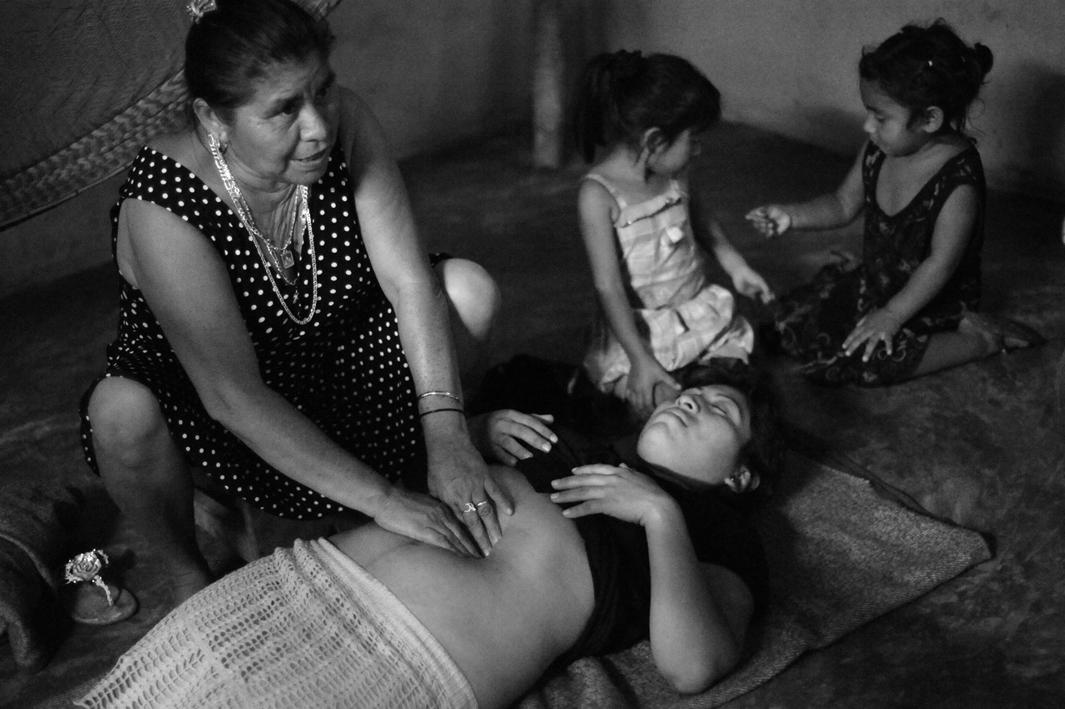 Traditional Mayan midwife Elsa Gonzalez Ayala shows CASA Midwifery School students how to perform a traditional Mayan massage used to shrink a woman's uterus and reduce post-partum bleeding - on Nelsi Marvella Tuk Balam.CASA Midwifery School students traveled to the rural village of Chunhuhub to learn traditional methods from traditional Mayan midwives and to teach them contemporary practices in exchange.