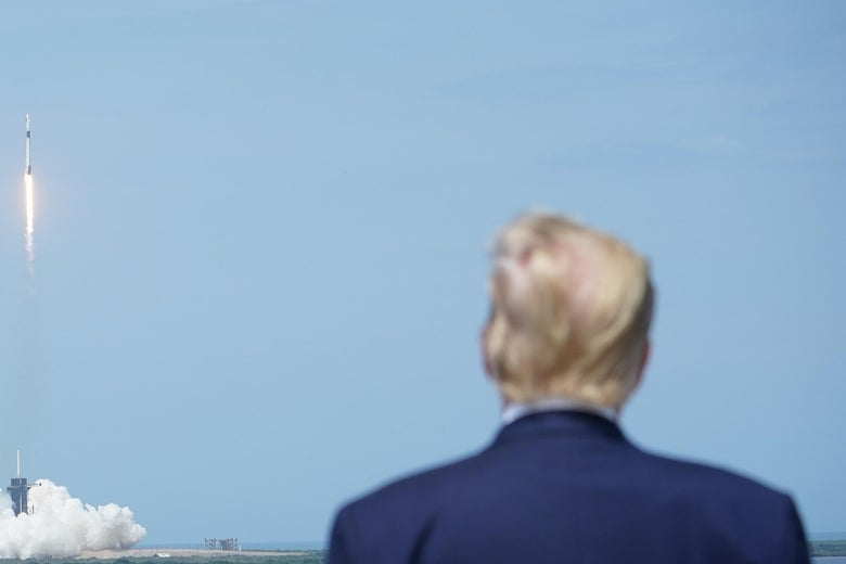 President Donald Trump watches the SpaceX Falcon 9 rocket carrying the SpaceX Crew Dragon capsule, with astronauts Bob Behnken and Doug Hurley, lift off from Kennedy Space Center in Florida on May 30, 2020.
