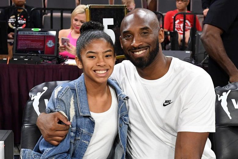 Gigi and Kobe Bryant sitting courtside and smiling. Kobe has his arm around Gigi.