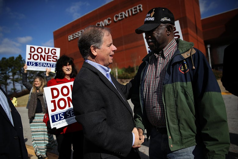 BESSEMER, AL - DECEMBER 12:  Democratic Senatorial candidate Doug Jones (L) greets voters outside of a polling station at the Bessemer Civic Center on December 12, 2017 in Bessemer, Alabama. Doug Jones is facing off against Republican Roy Moore in a special election for U.S. Senate.  (Photo by Justin Sullivan/Getty Images)