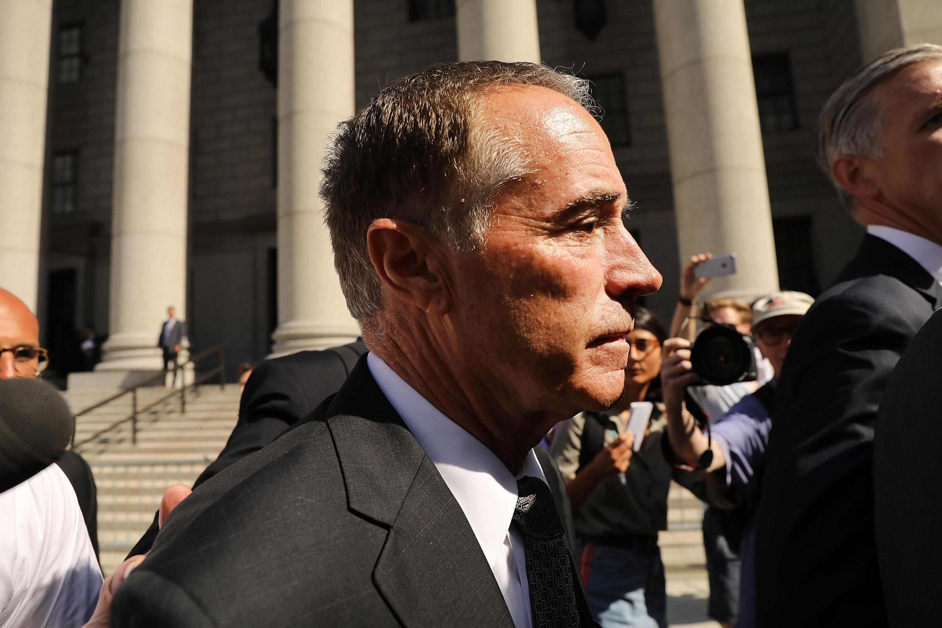 Chris Collins outside a courthouse, surrounded by cameras