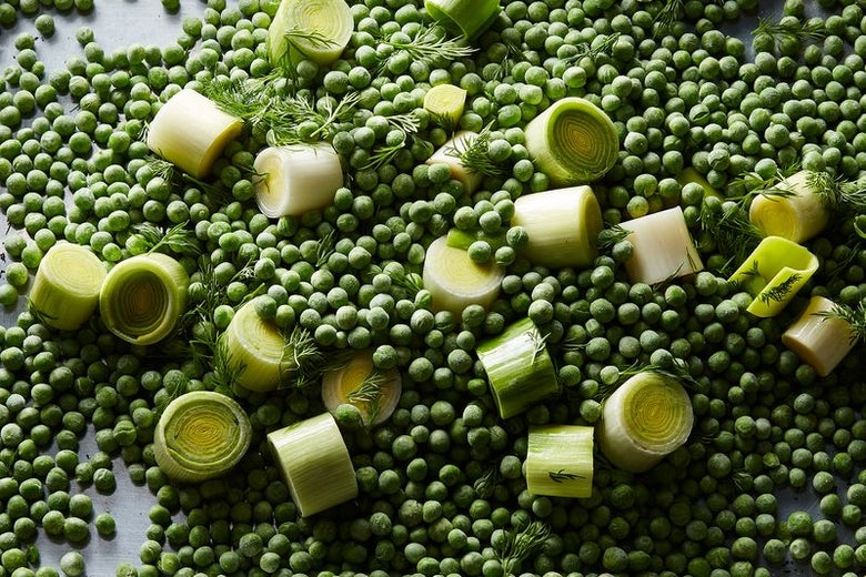 Leek slices and sprigs of fresh dill sit on a bed of green peas.