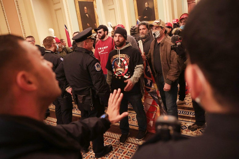 Multiple maskless and masked Trump supporters gather inside the Capitol Building. Capitol Police officers engage with them.