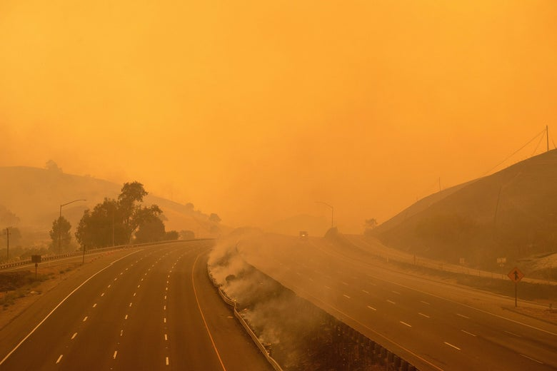 A firetruck drives along a highway amid wildfire smoke.