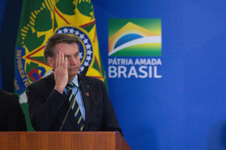Bolsonaro, at a lectern, holds a hand by his head.