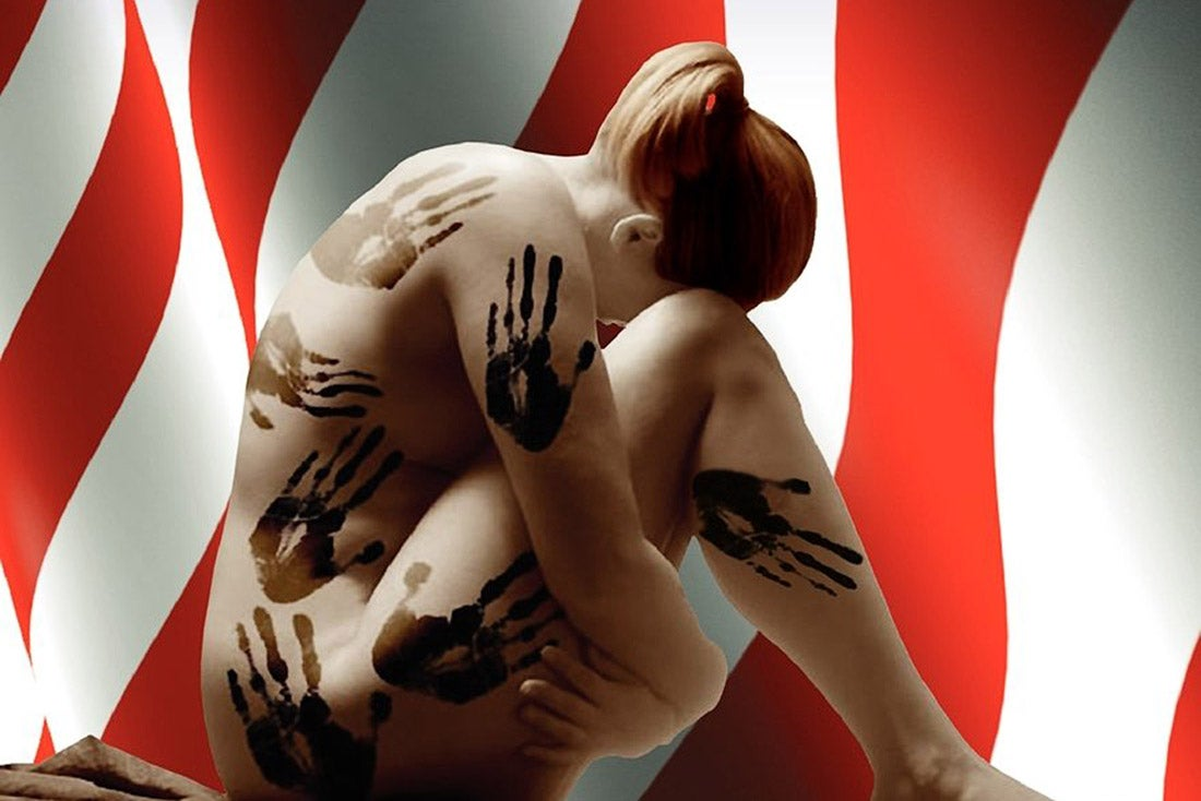 A naked white woman with red hair is covered with black handprints.