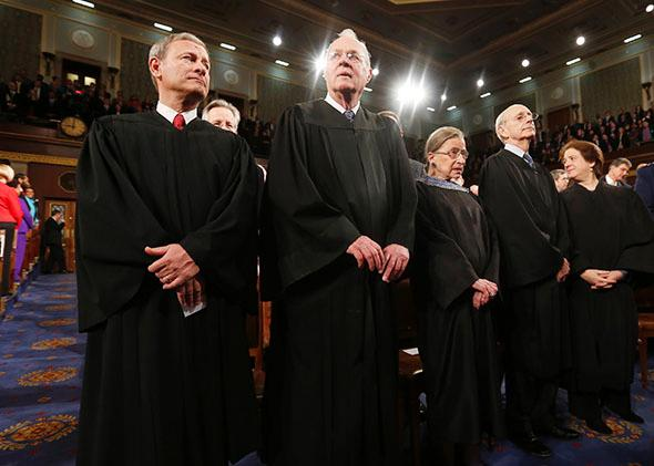 U.S. Supreme Court Chief Justice John Roberts (L) stands with fellow Justices Anthony Kennedy (2nd from L), Ruth Bader Ginsburg, Stephen Breyer and Elena Kagan.
