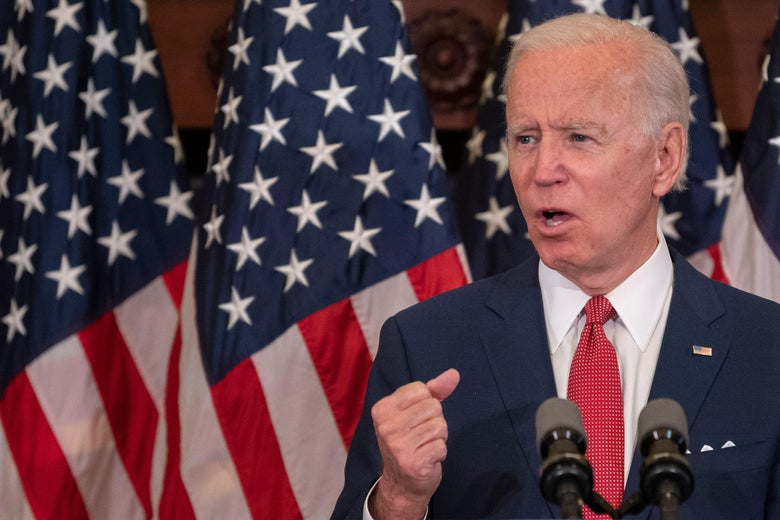 Biden speaks at a mic in front of American flags
