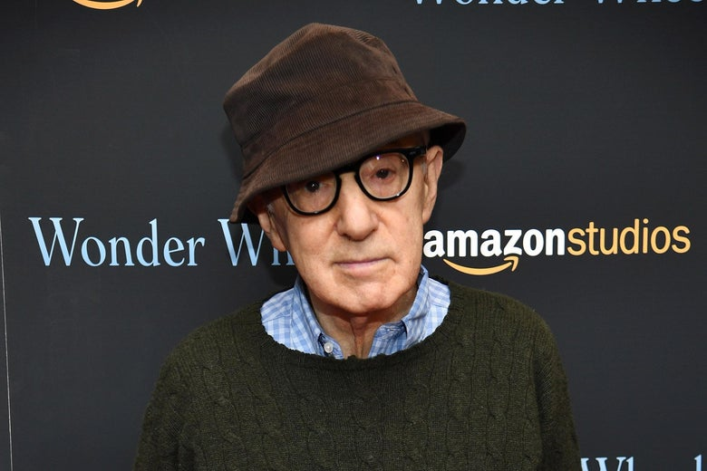 "Woody Allen wears a brown bucket hat and black glasses as he poses in front of a backdrop the says ""Wonder Wheel"" and ""Amazon Studios."""