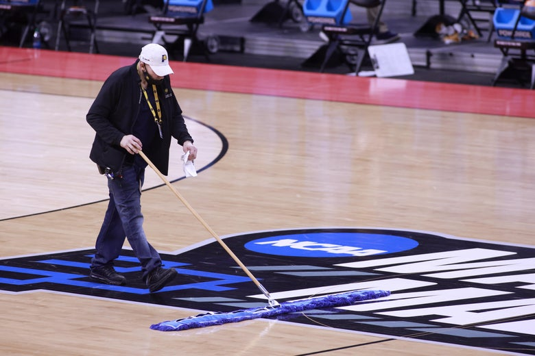 A man sweeps the basketball court with the March Madness logo on it, in Indianapolis