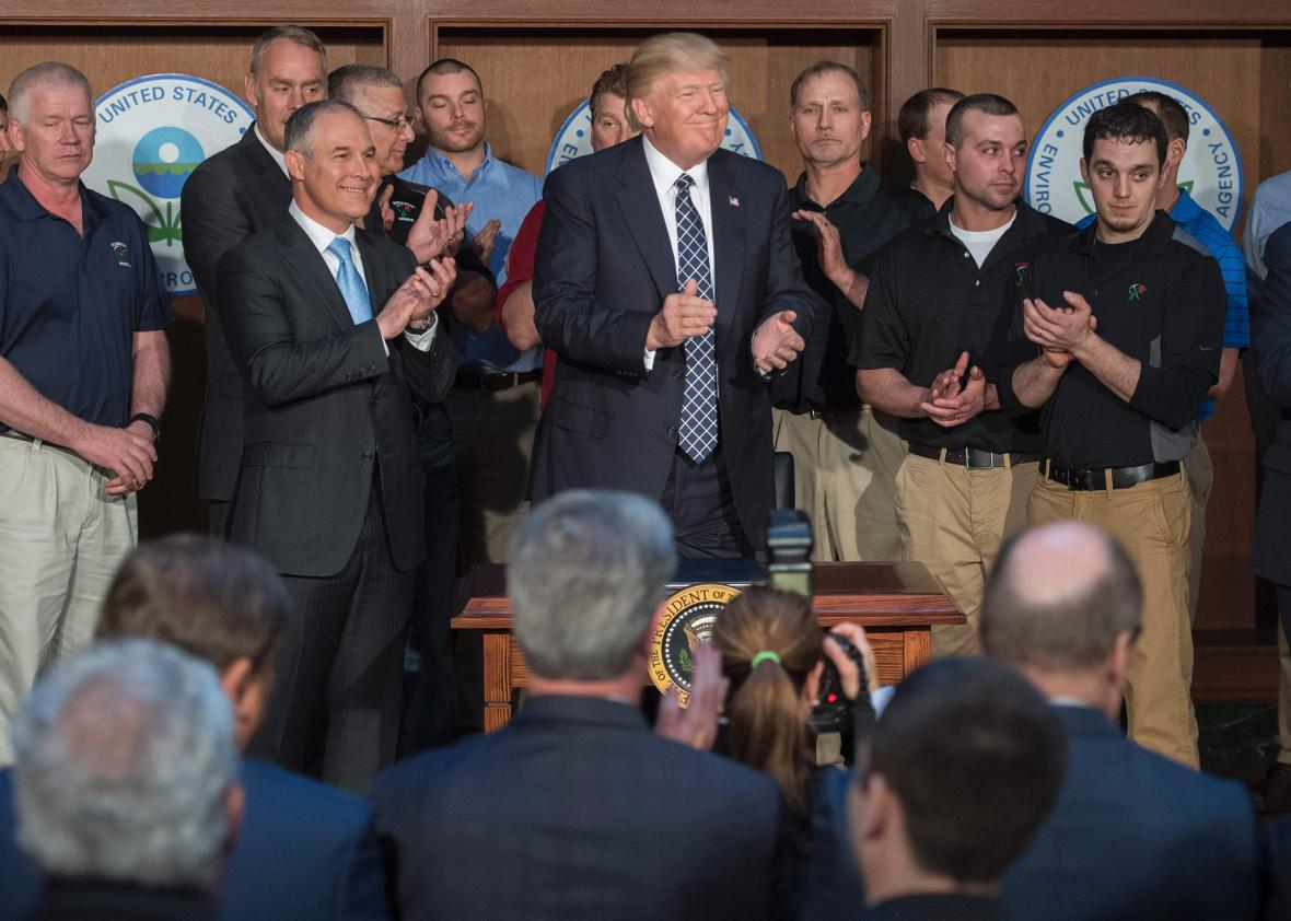 Surrounded by miners from Rosebud Mining, US President Donald Trump (C) applauds after signing the Energy Independence Executive Order at the Environmental Protection Agency