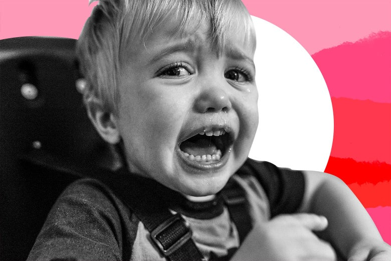 A toddler in his high chair, crying.