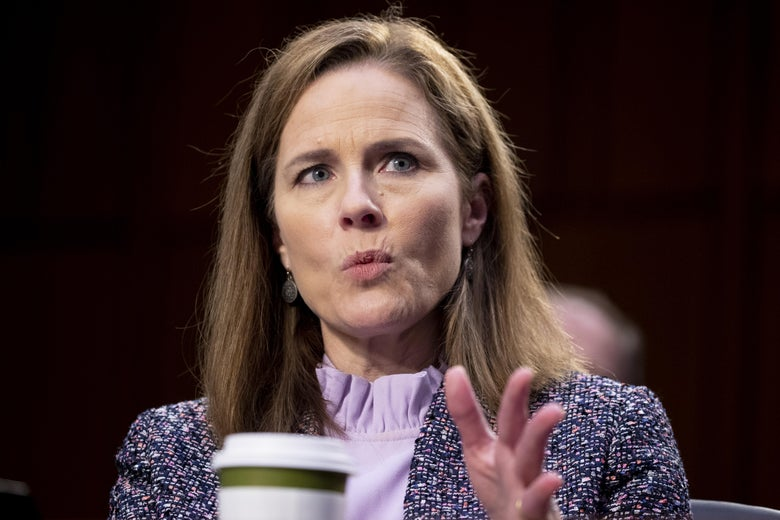 Amy Coney Barrett speaks while gesturing. A coffee cup can be seen in front of her.