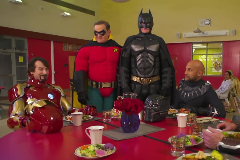 Iron Man, Robin, Batman, and Black Panther sit at a cafeteria table.